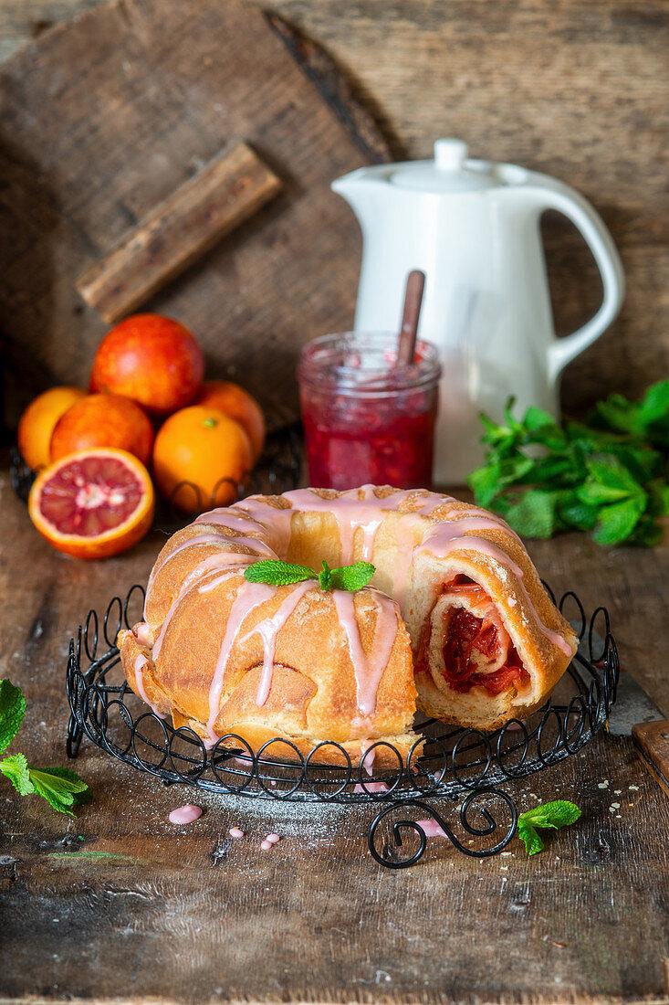 Yeast cake with blood orange jam filling and glaze