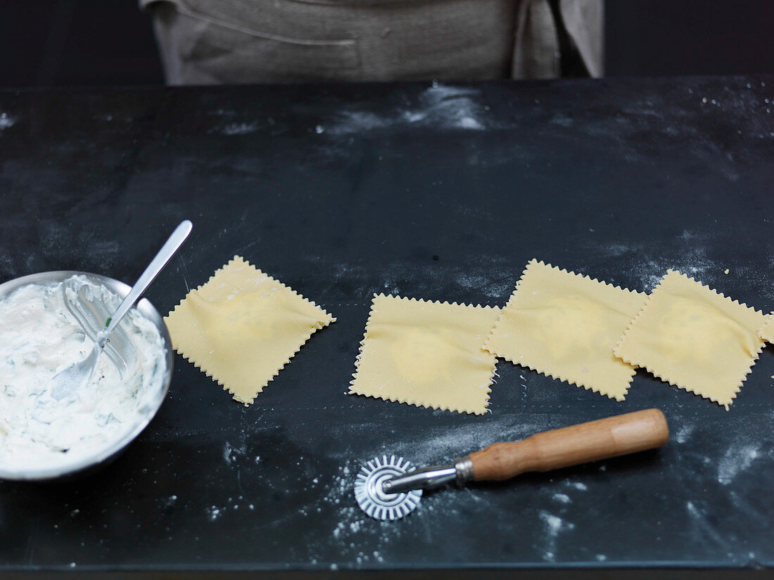 Preparing filled pasta: cut out ravioli with a pastry wheel