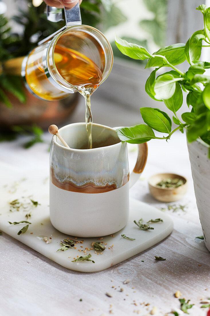 Pouring herbal tea into a tea cup
