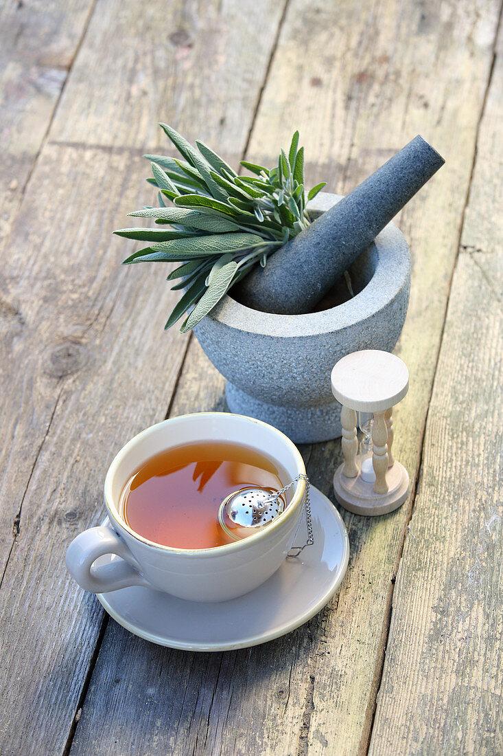 Sage tea and fresh sage in a mortar