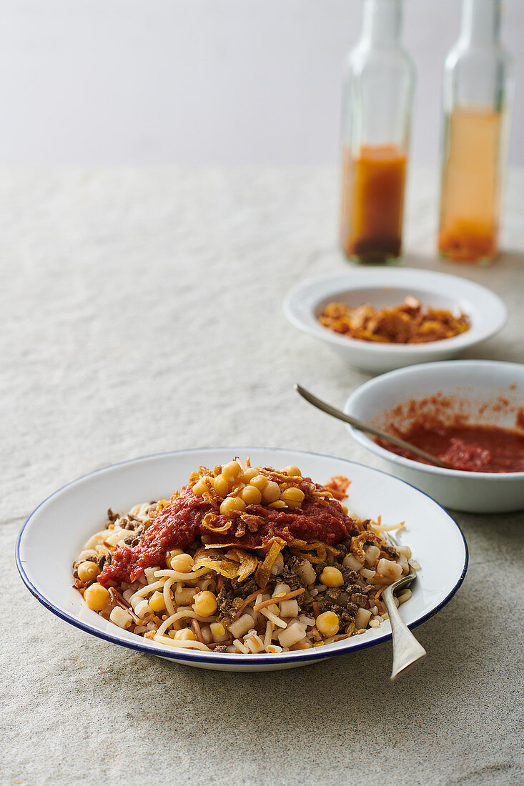 Koshari Traditional Egyptian dish - vegan mixed rice, pasta, lentils, with caramelized onions and tomato chili sauce