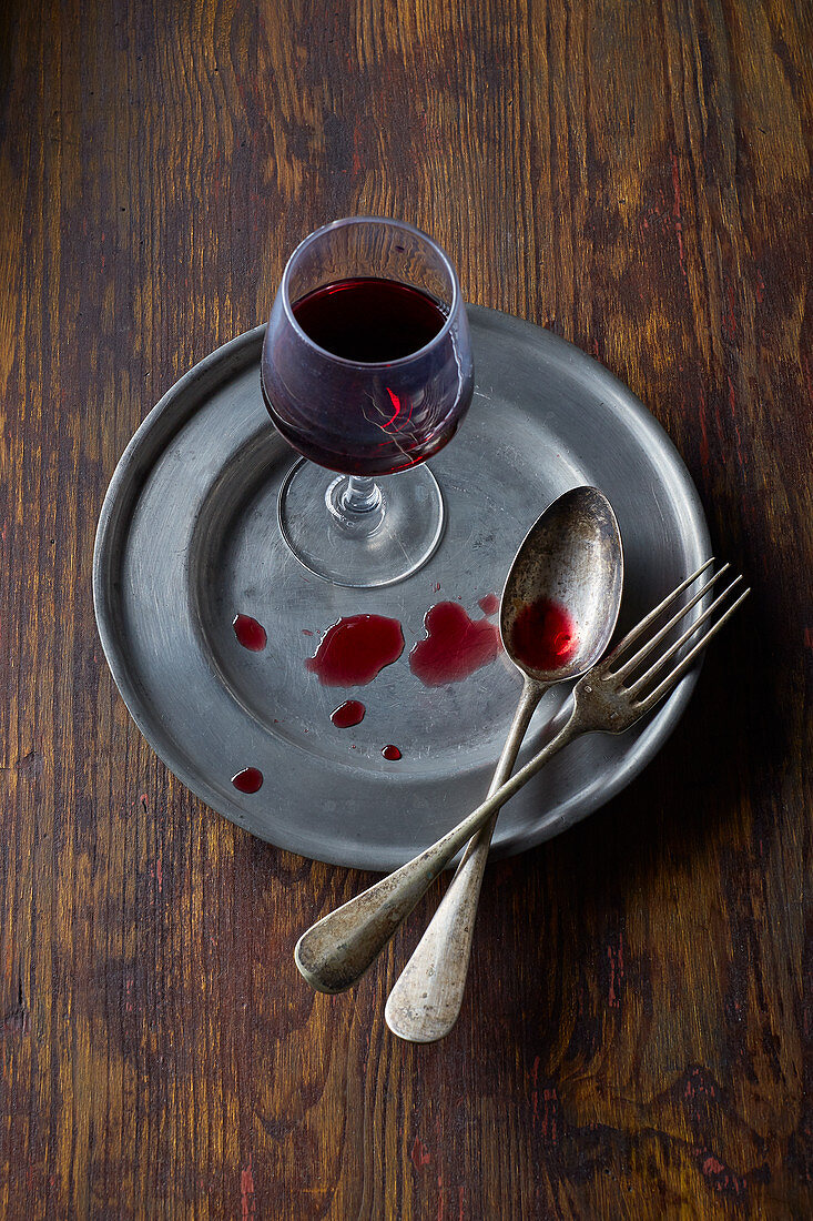 Red wine glass on a metal plate with cutlery