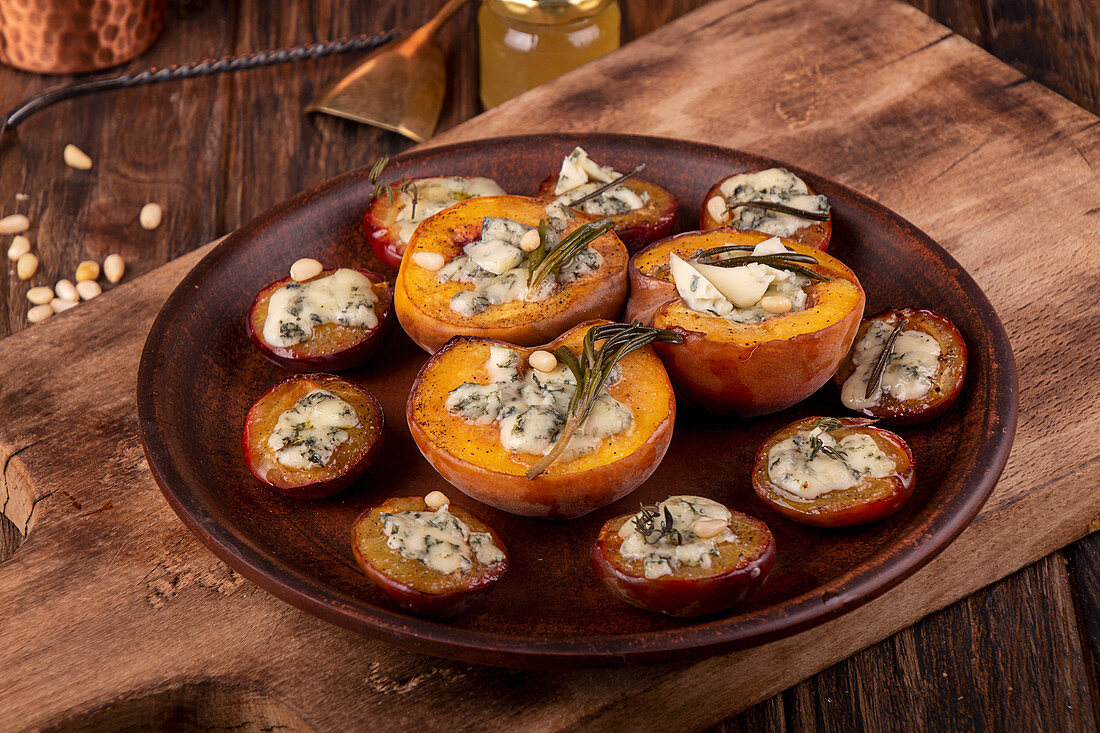 Grilled baked peach and plums stuffed with blue cheese dorblu and rosemary