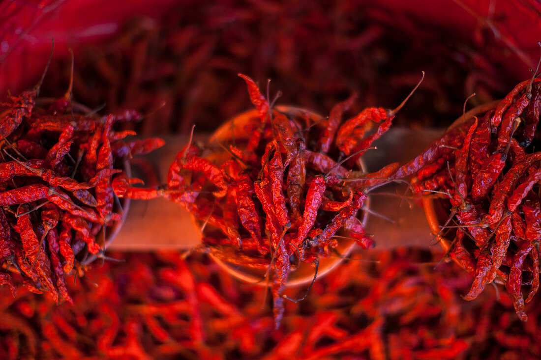 Top view of dried red hot chili peppers arranged in pots for sale on market