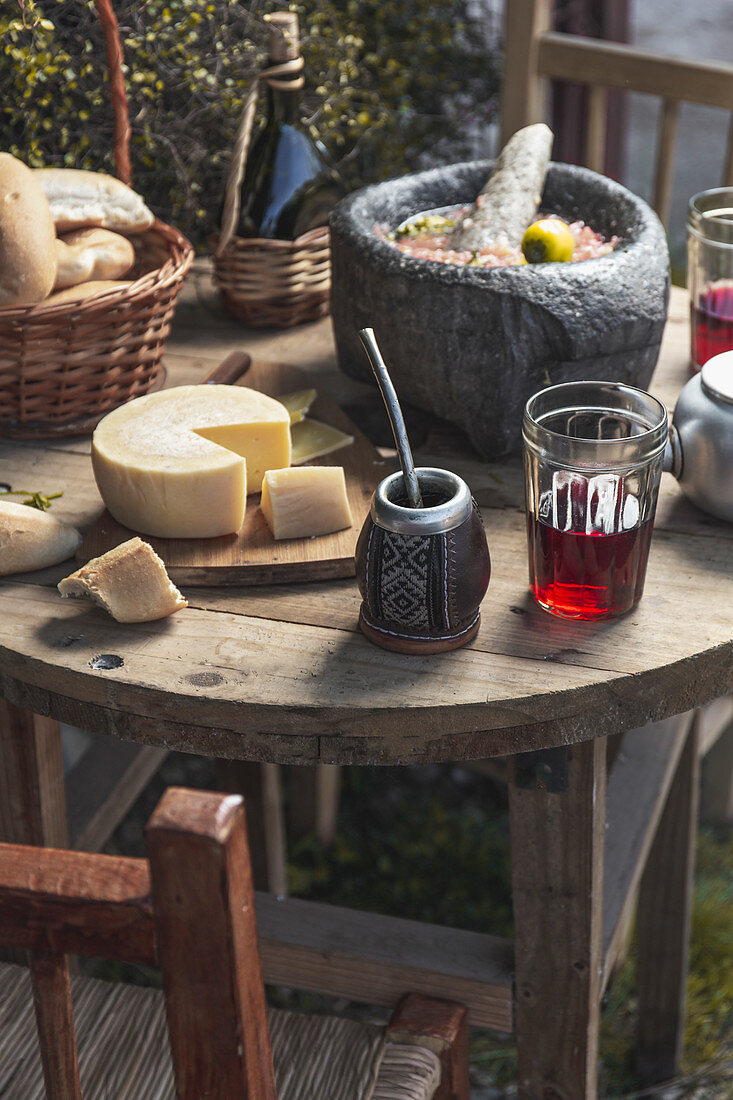 Rustic Table with Latin American Chilean tipical dishes Tomato Sause - Salsa in stone mortar, Yerba Mate, Red wine