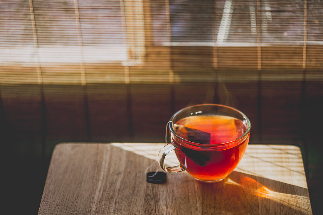 A cup of hot tea on sunny day near a window.