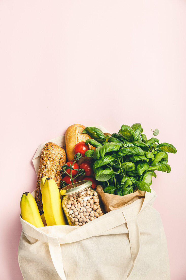 Flat-lay of healthy grocery shopping eco-friendly bag with fresh vegetables, fruit, bread, herbs and legumes