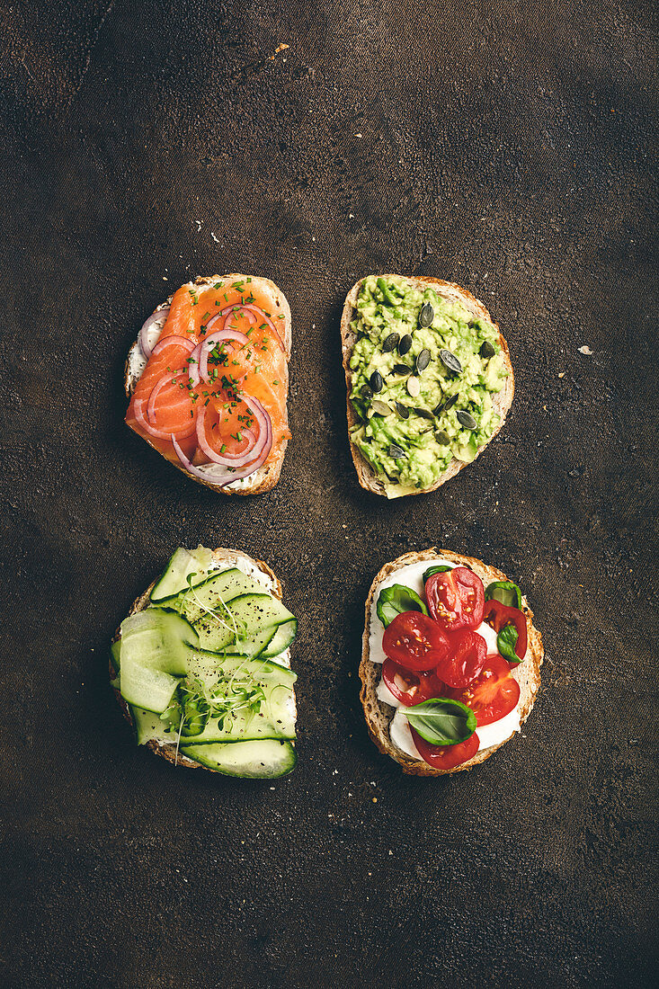 Variety of sandwiches for breakfast, snack, appetizers - avocado puree, mozzarella, tomatoes, basil, cream cheese, smoked salmon, red onion, cucumber whole grain bread sandwiches