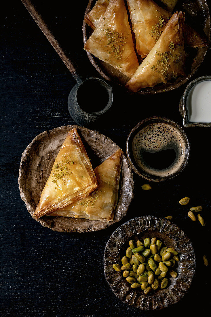 Homemade Turkish traditional dessert baklava with pistachio served on ceramic plate with bowl of nuts, cup of coffee, cream, cezva