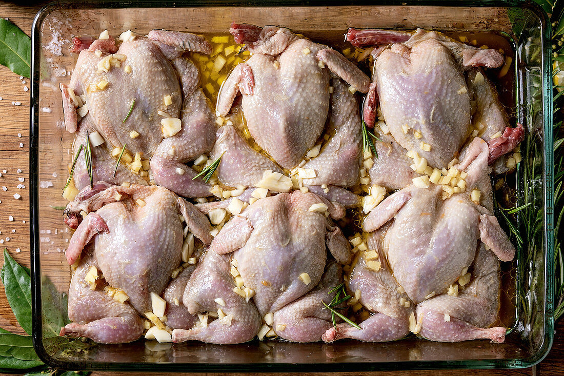 Raw uncooked quails butterfly in marinade in glass baking tray with lime, salt, pepper, olive oil, garlic and greens
