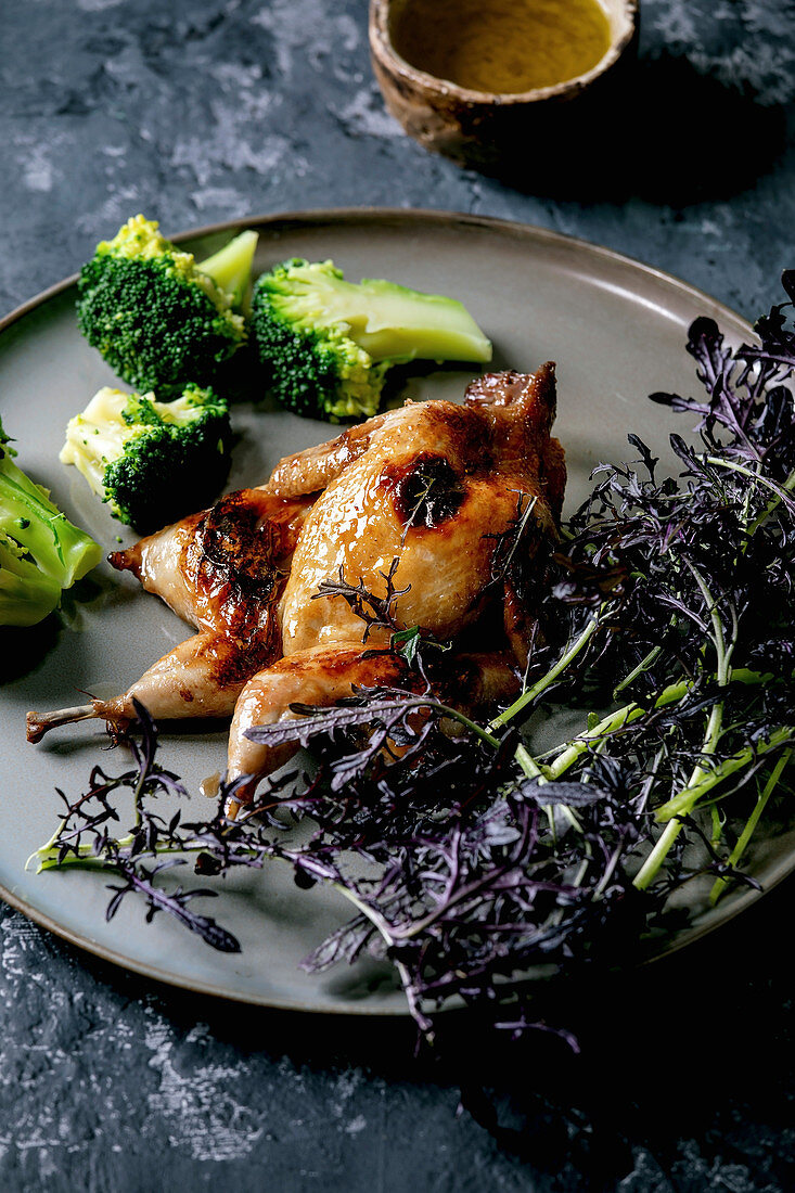 Roasted grilled butterfly quail on ceramic plate with garnish green salad and broccoli, pepper mill and olive oil