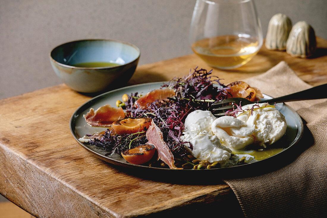 Salad with traditional italian burrata cheese, black arugula, grilled apricot, prosciutto, pistachio nuts and olive oil