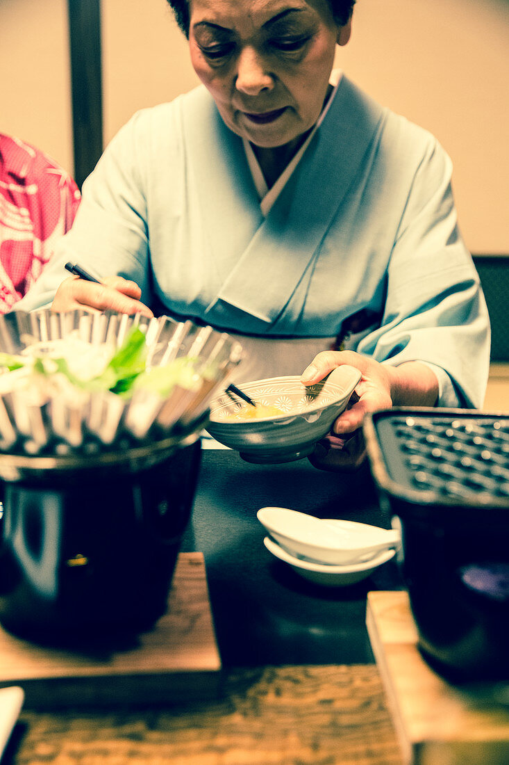 Japanese woman in kimono serving kaiseki
