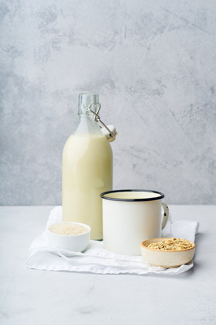 Rice milk and oat milk in a bottle and an enamel mug