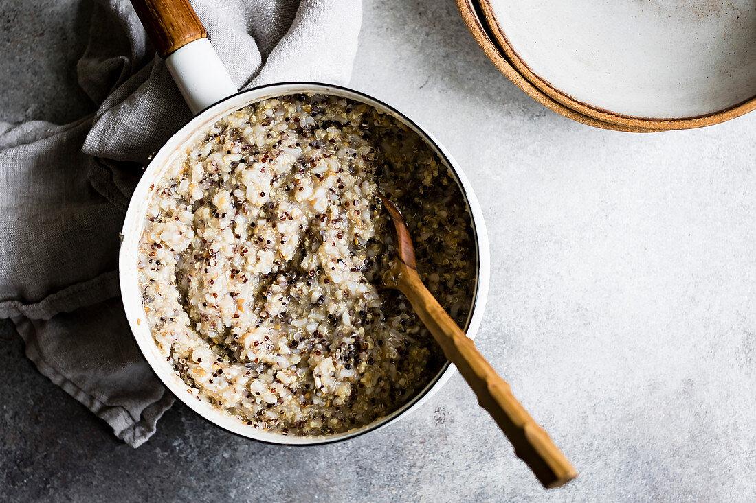 Multigrain porridge in a saucepan with wooden spoon