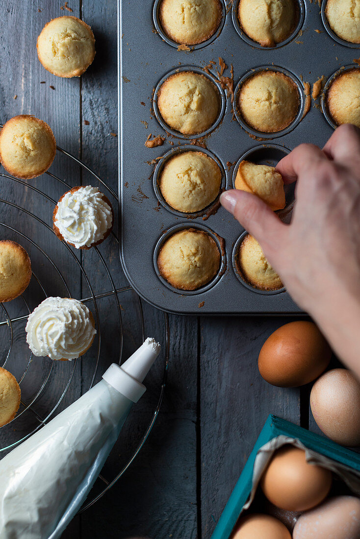 Garnishing mini muffins in a baking dish with whipped cream