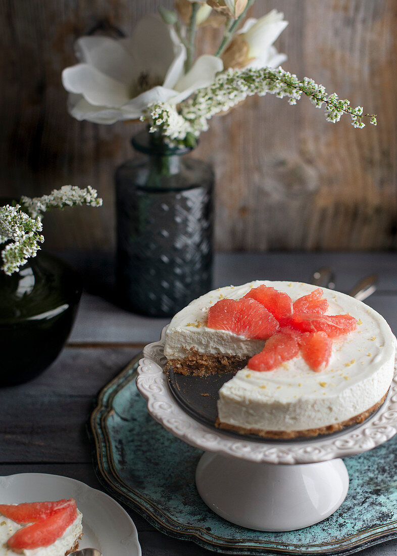 No bake cheesecake with pink grapefruit on a cake stand