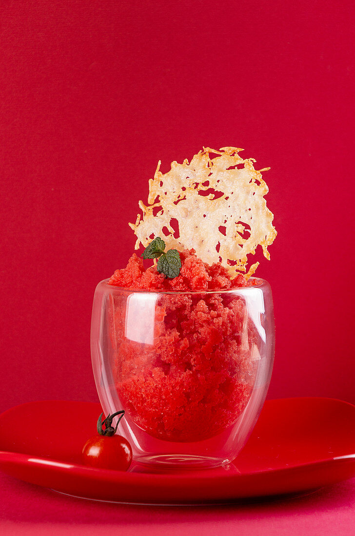 Fresh tomato sorbet glass decorated with cheese crisp over on red plate on red background