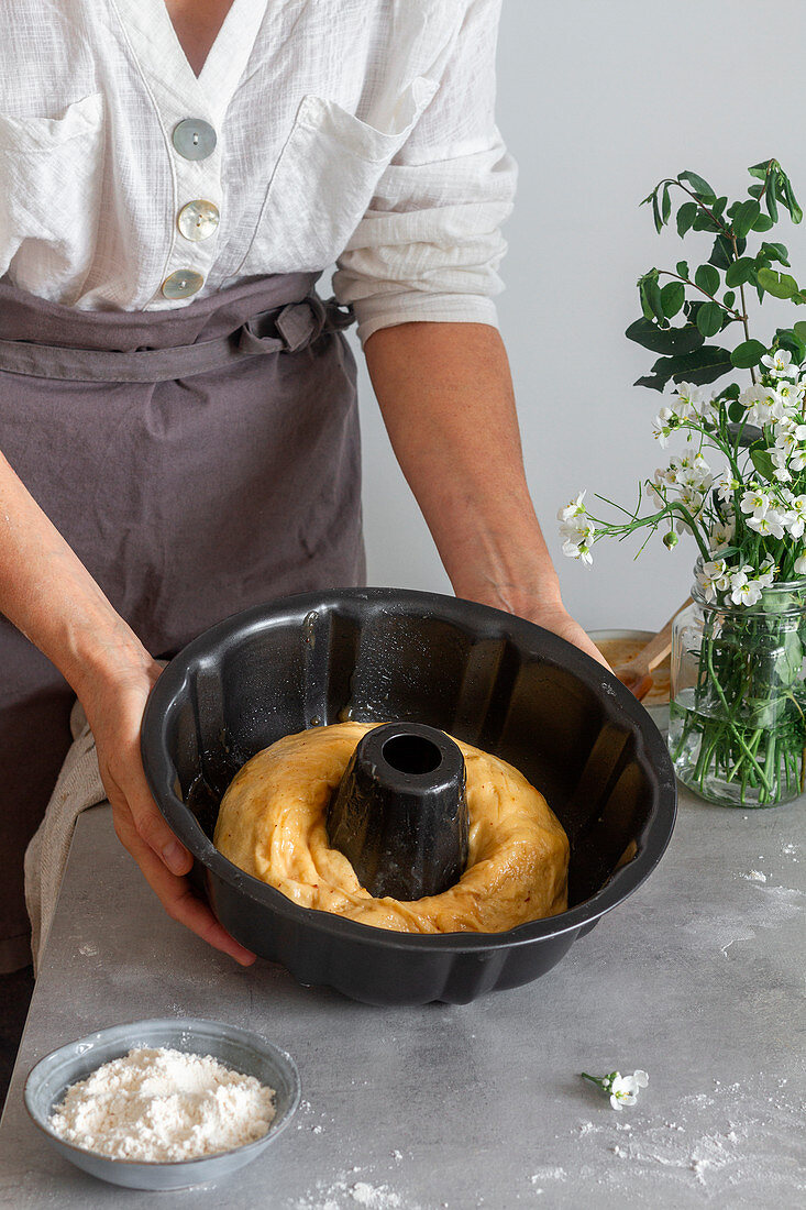 Unrecognizable female in apron showing off roll of soft dough into pan