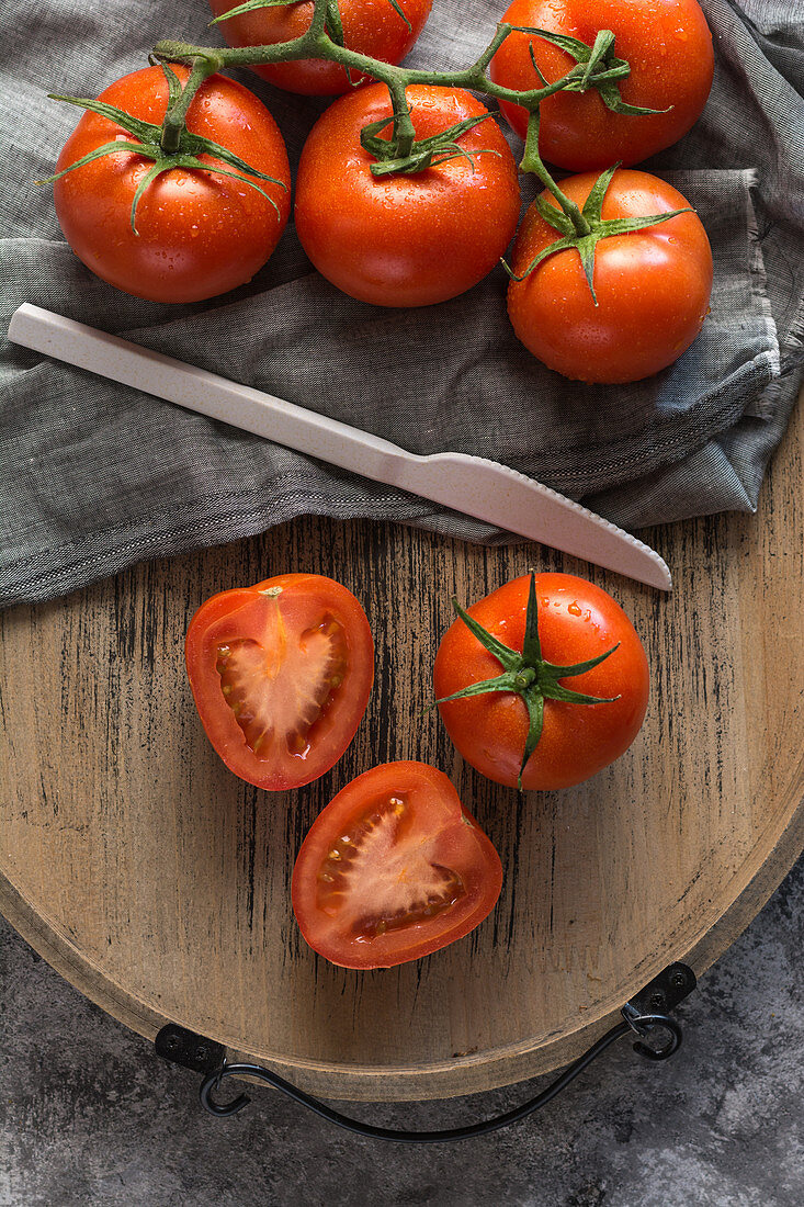 Halved and whole fresh tomatoes placed wooden board on rough gray table