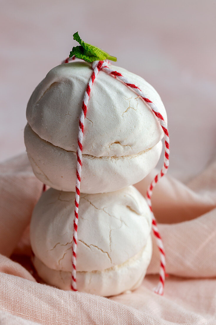 Homemade white Zefir traditional russian dessert hold by a small rope on pink background