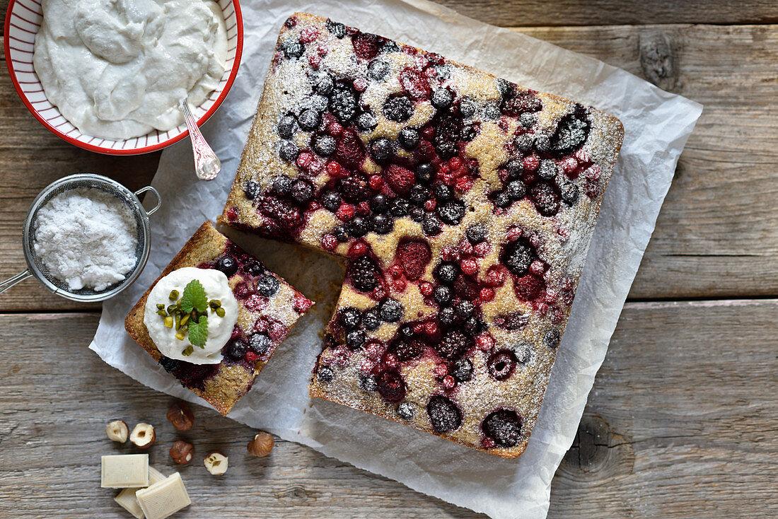 Veganer Griess-Haselnuss-Kuchen mit Beeren und weisser Schokoladen-Frischkäse-Creme