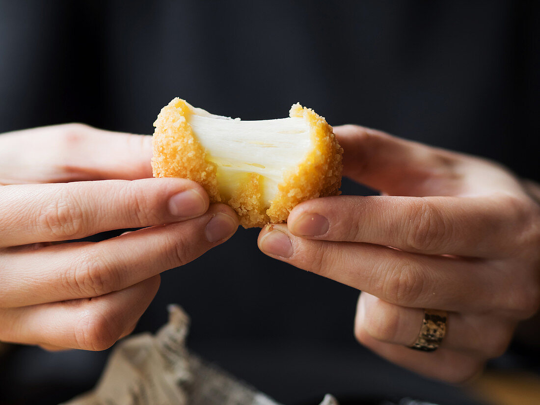 Crop unrecognizable female hands holding delicious mozzarella cheese ball