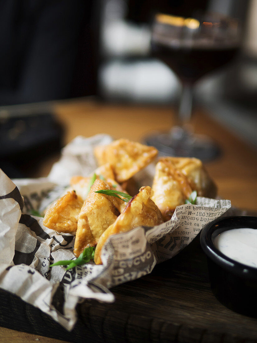 Deep fried dumplings garnished with green herbs placed on paper served with white sauce