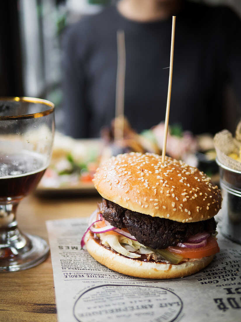 Appetizing beef burger with tomato and onion made with wheat buns with sesame served on paper