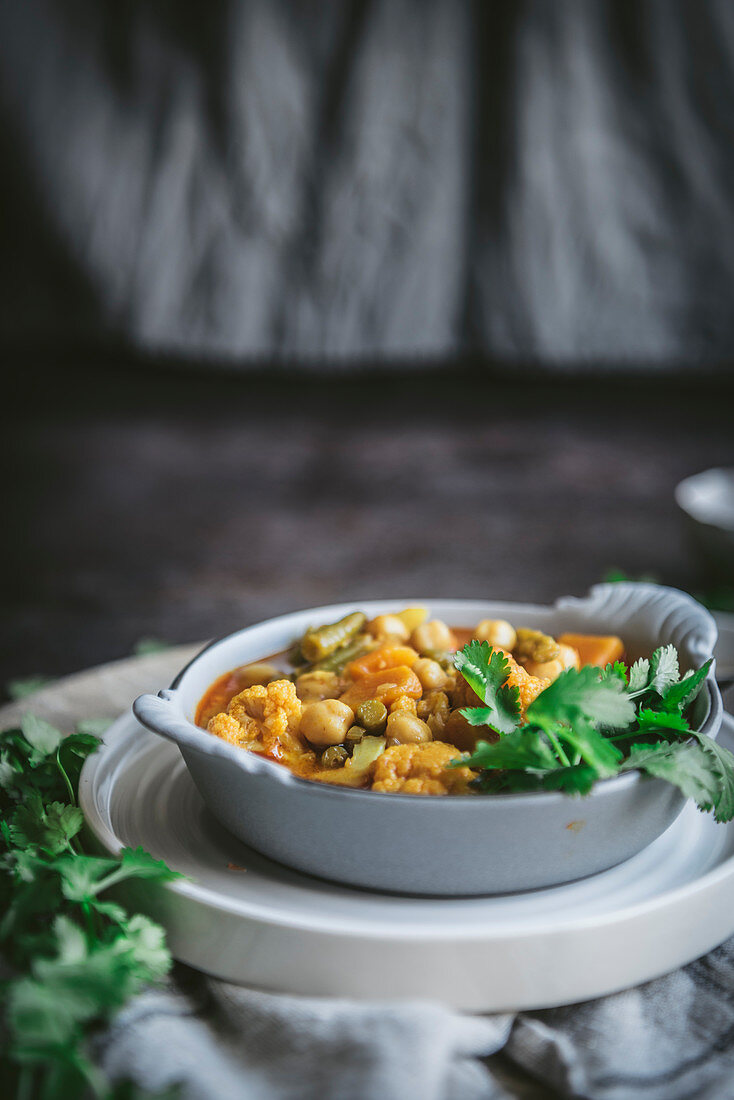 Bowl with tasty chickpea curry and herbs