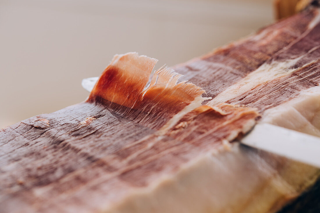 Knife cutting thin slice of ham with tallow lines