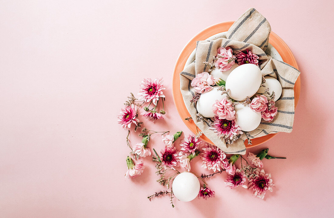 Bunch of delicate flowers arranged near plate with chicken eggs on Easter Day on pink background