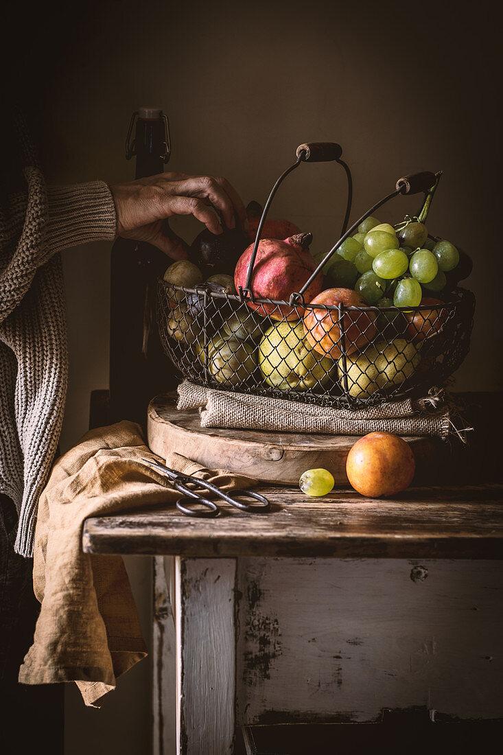 Frauenhand greift nach reifem Obst in einem Obstkorb