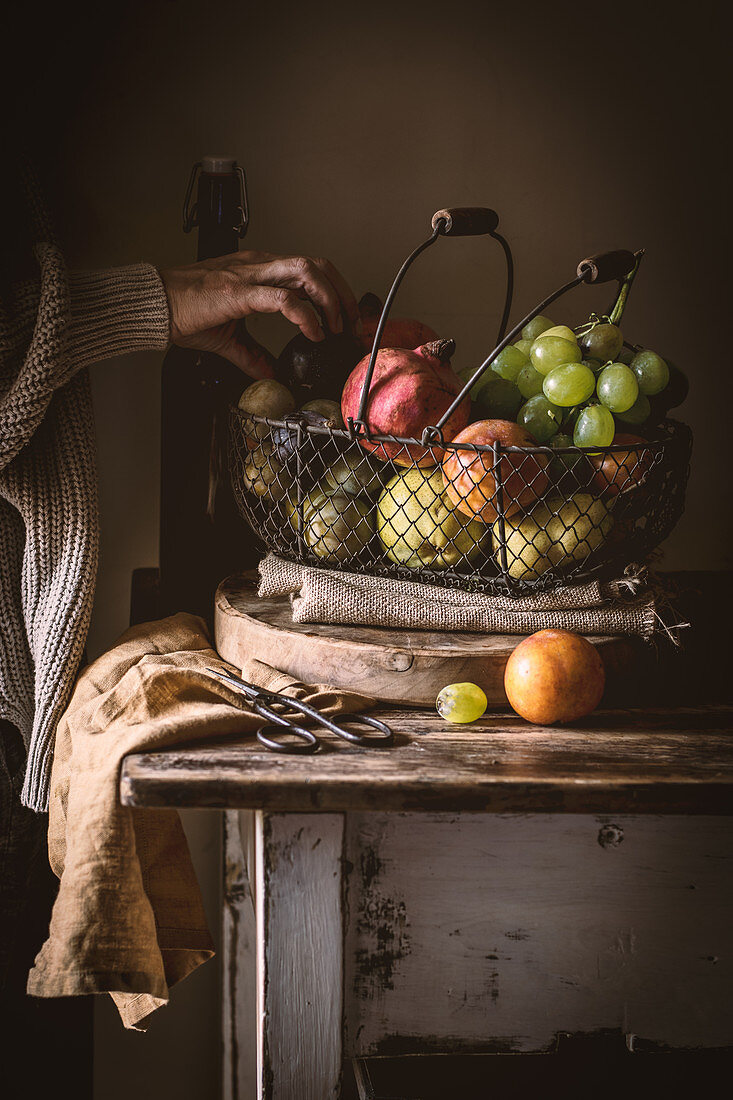 Unrecognizable elderly person taking ripe fruit from metal basket on rustic table