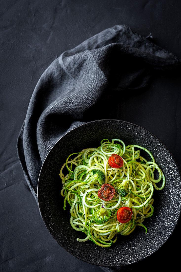 Homemade Zucchini Spaghetti with pesto sauce, broccoli and cherry tomatoes