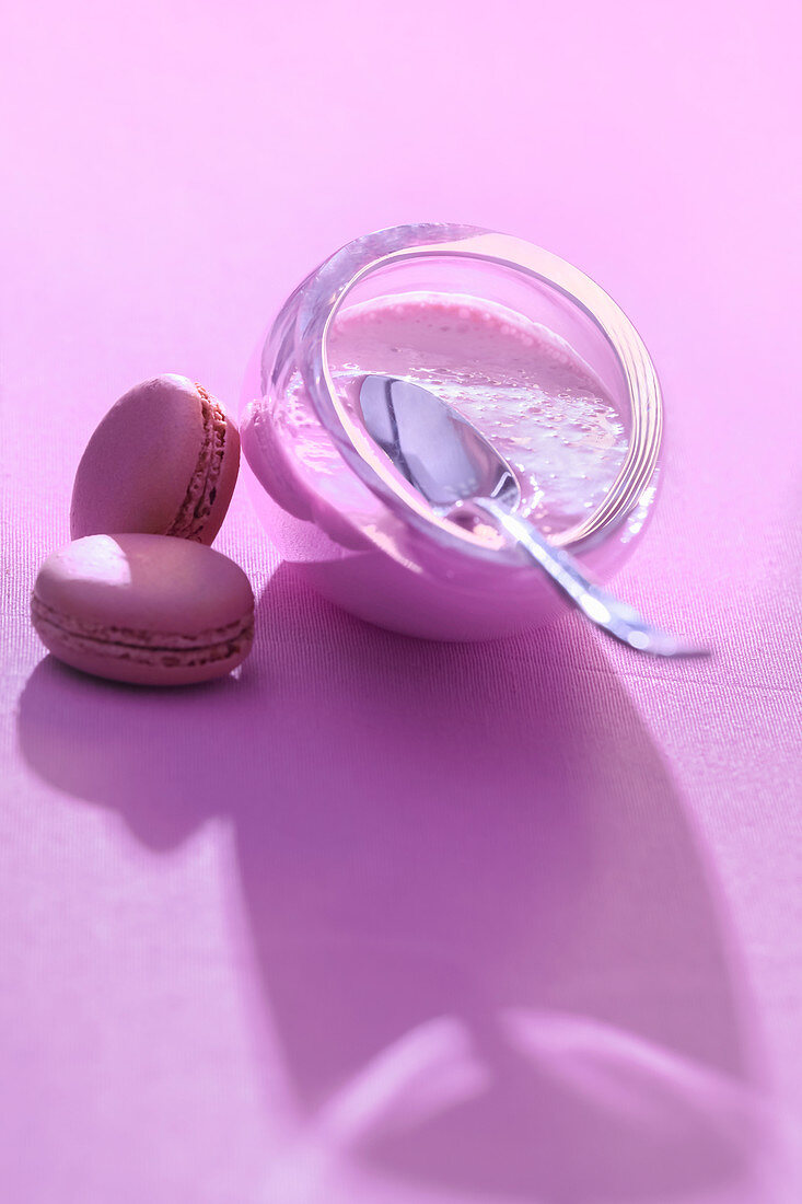 Glass bowl of delicious healthy dairy dessert with fresh sweet round glazed cookies on table in delicate purple light