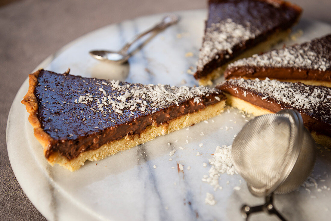 Chocolate tart with grated coconut, sliced
