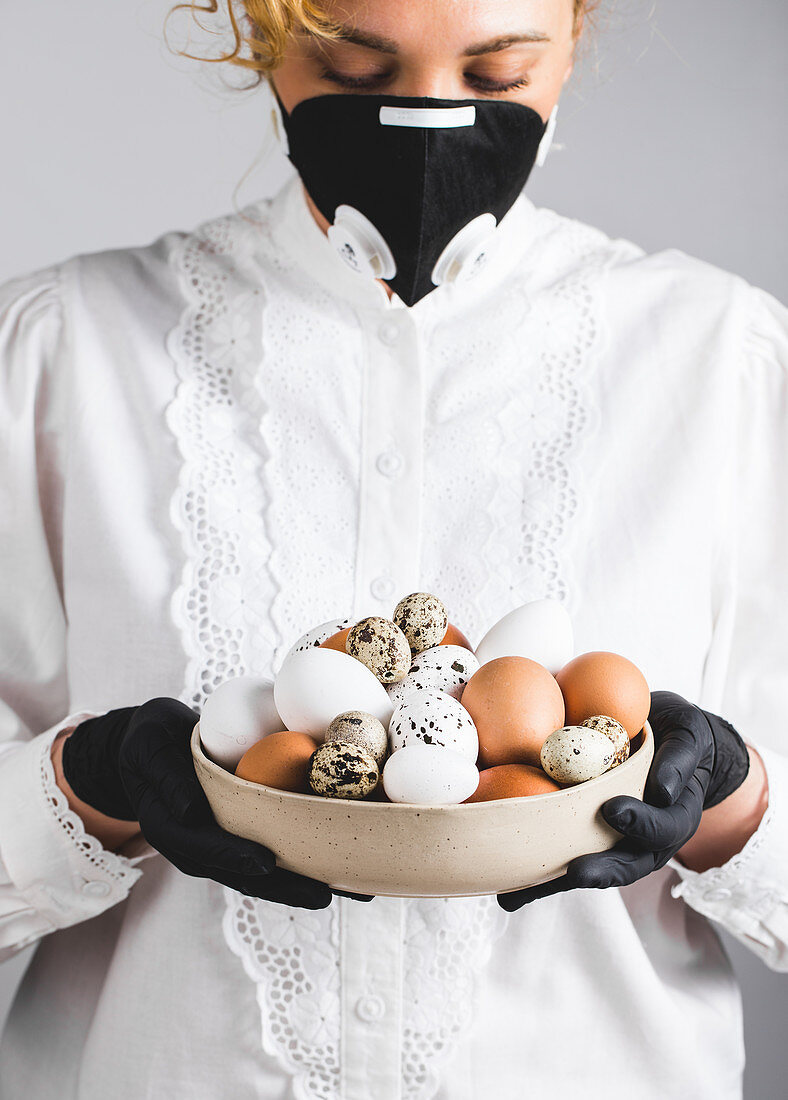 A woman wearing a white blouse and a black face mask and gloves holding a bowl of eggs