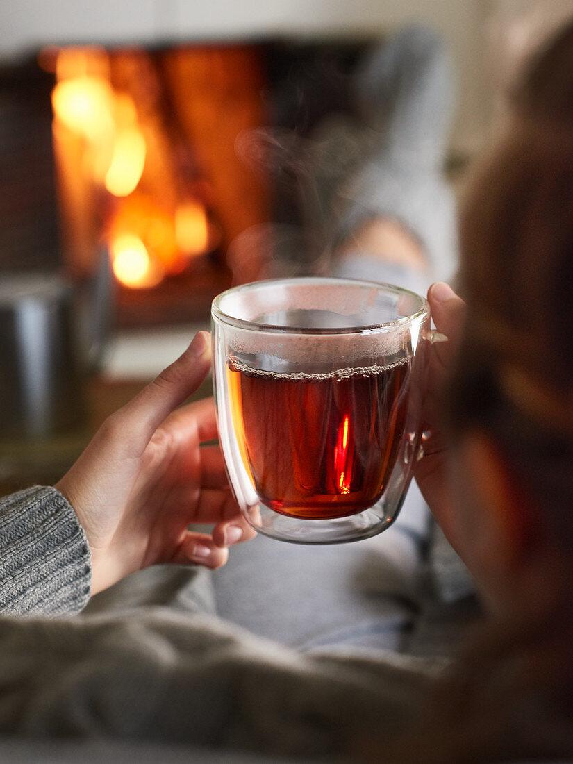 Eine heiße Tasse Tee am lodernden Kamin genießen
