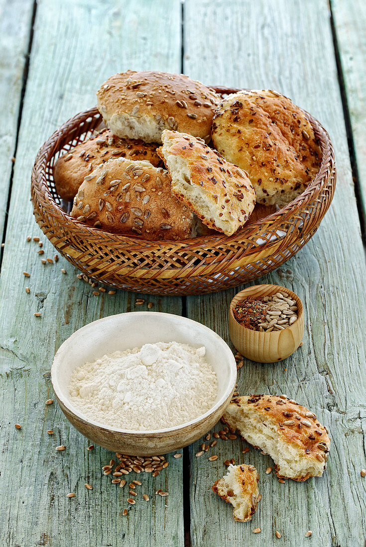Rolls in a bread basket with flour and seeds