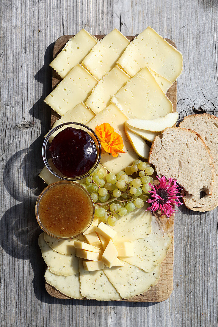 A cheese platter with alpine cheese, mustard dips, grapes and bread
