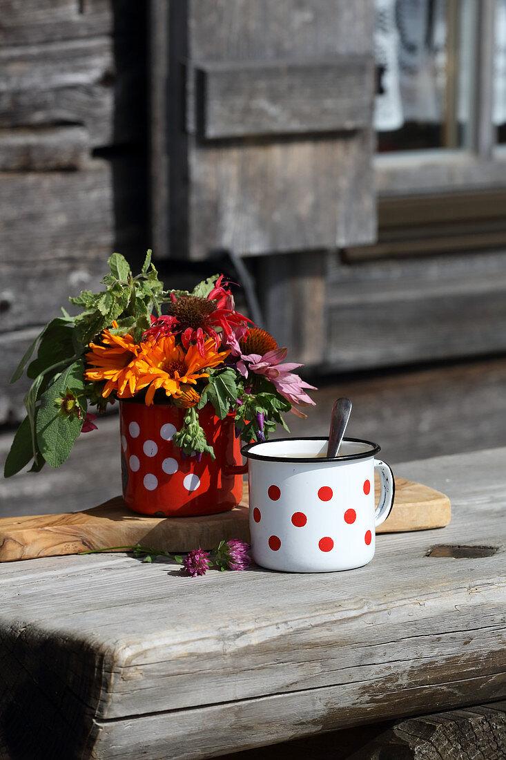 Emailletasse und Blumensträußchen auf Holztisch vor Almhütte