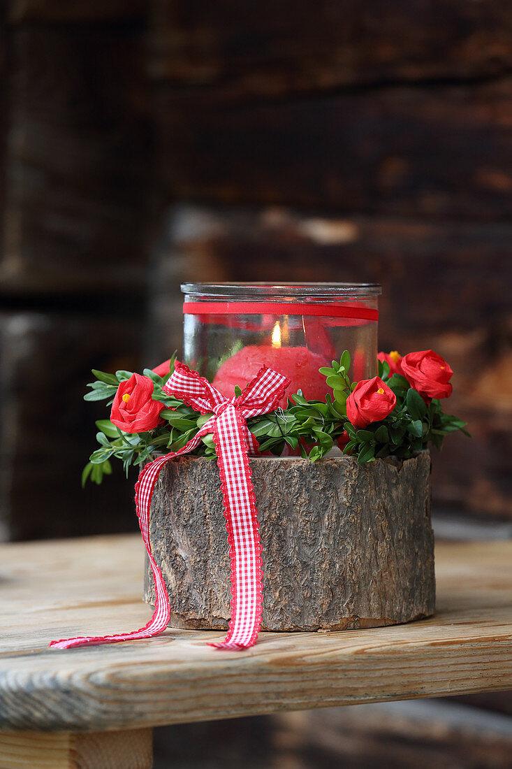 Windlicht auf Baumscheibe dekoriert mit selbstgemachten Kreppblumen