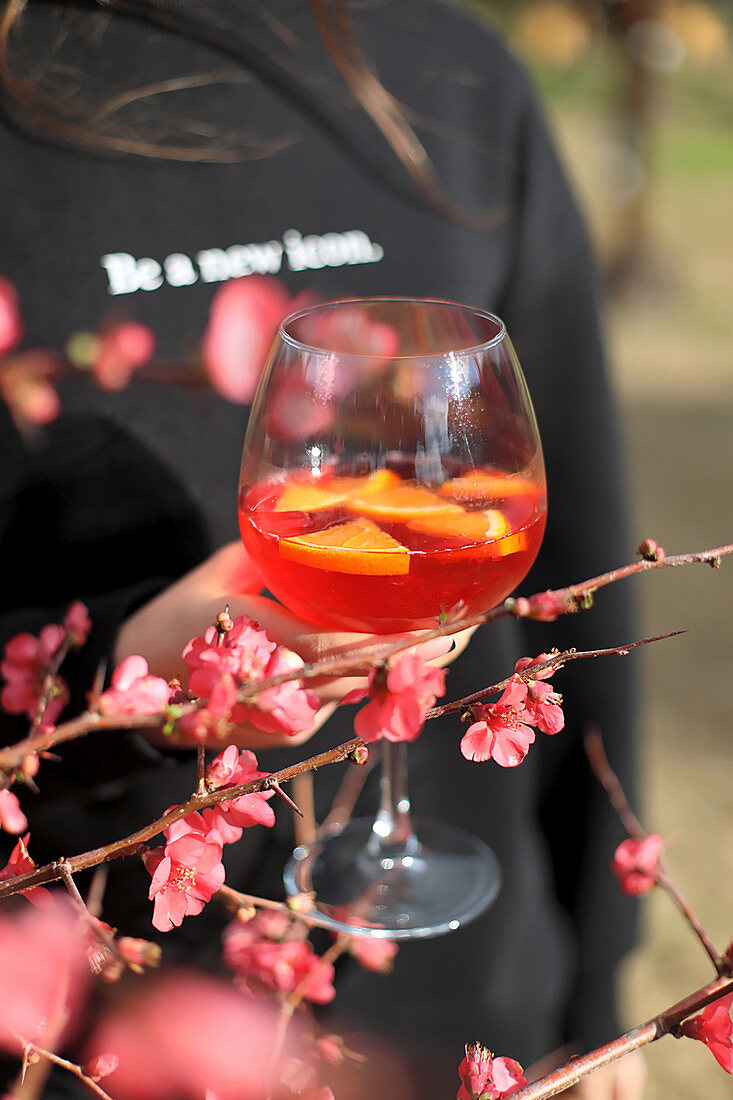 A hand holding a glass of Aperol Spritz with a sprig of blossom in the foreground