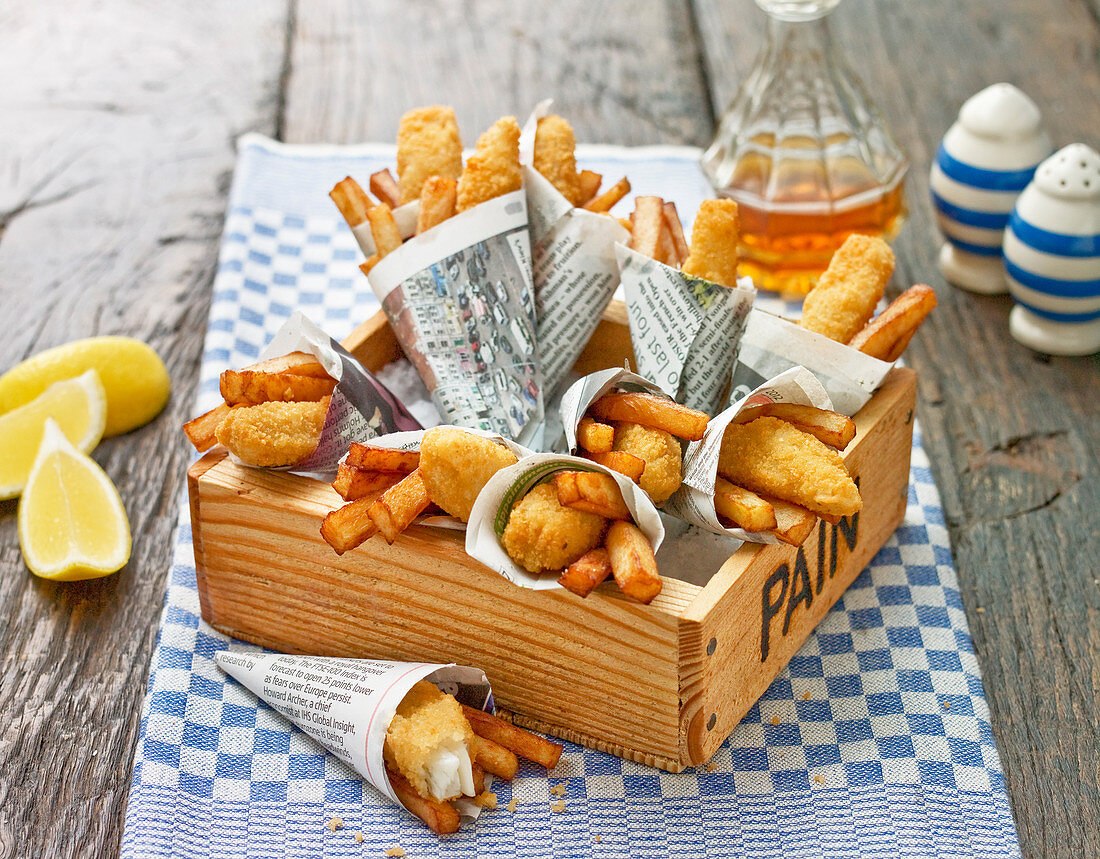Fish and Chips as finger food, wrapped in newspaper, in a wood tray