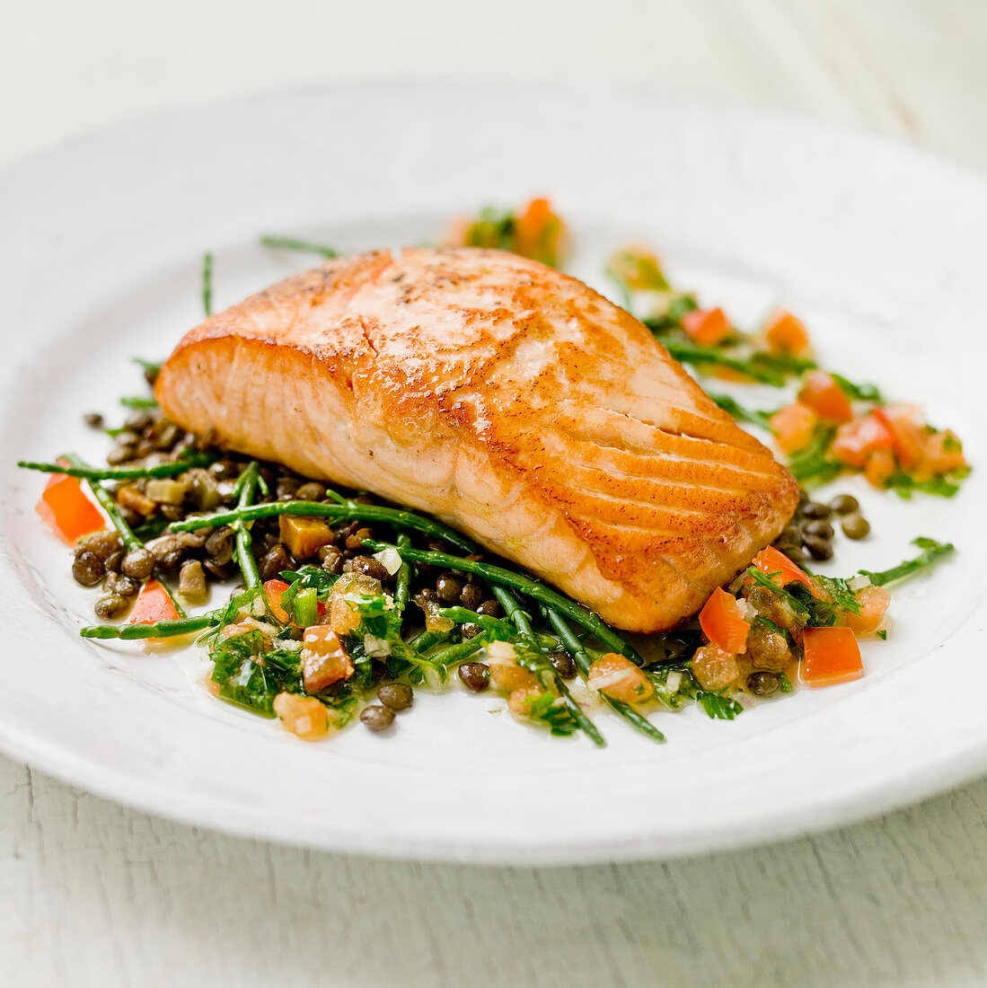 Salmon fillet on a bed of samphire, green lentles and tomatoes with a green herb vinegarette