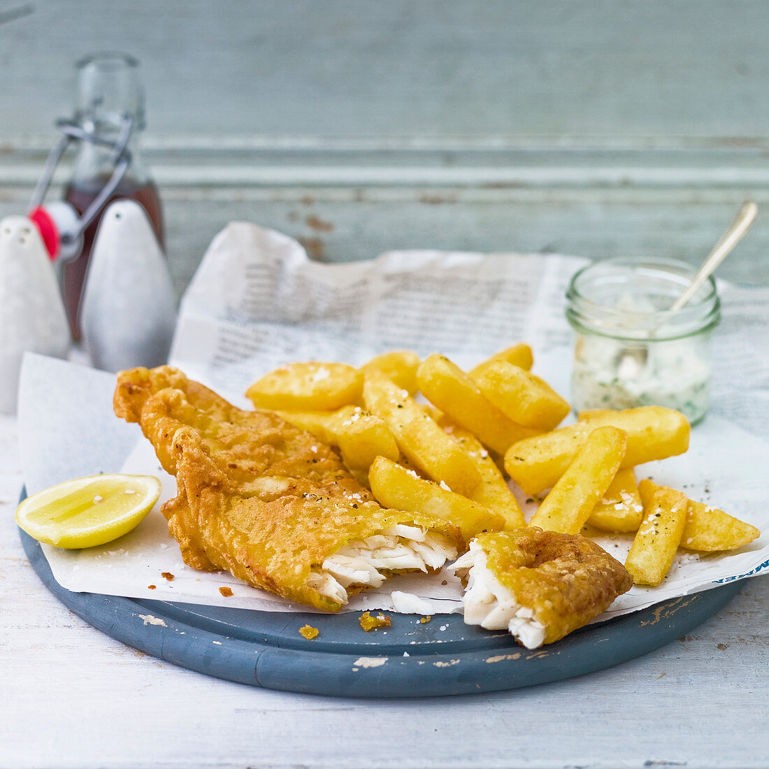 Fish and chips, battered cod with chunky chips, a slice of lemon, a pot of Tartare sauce