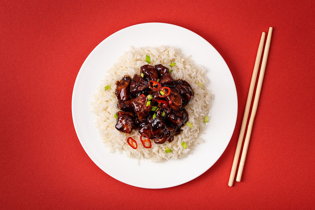 Sweet and sour meat stir fry in sticky sauce with rice on white plate with wooden chopsticks, traditional Chinese dish