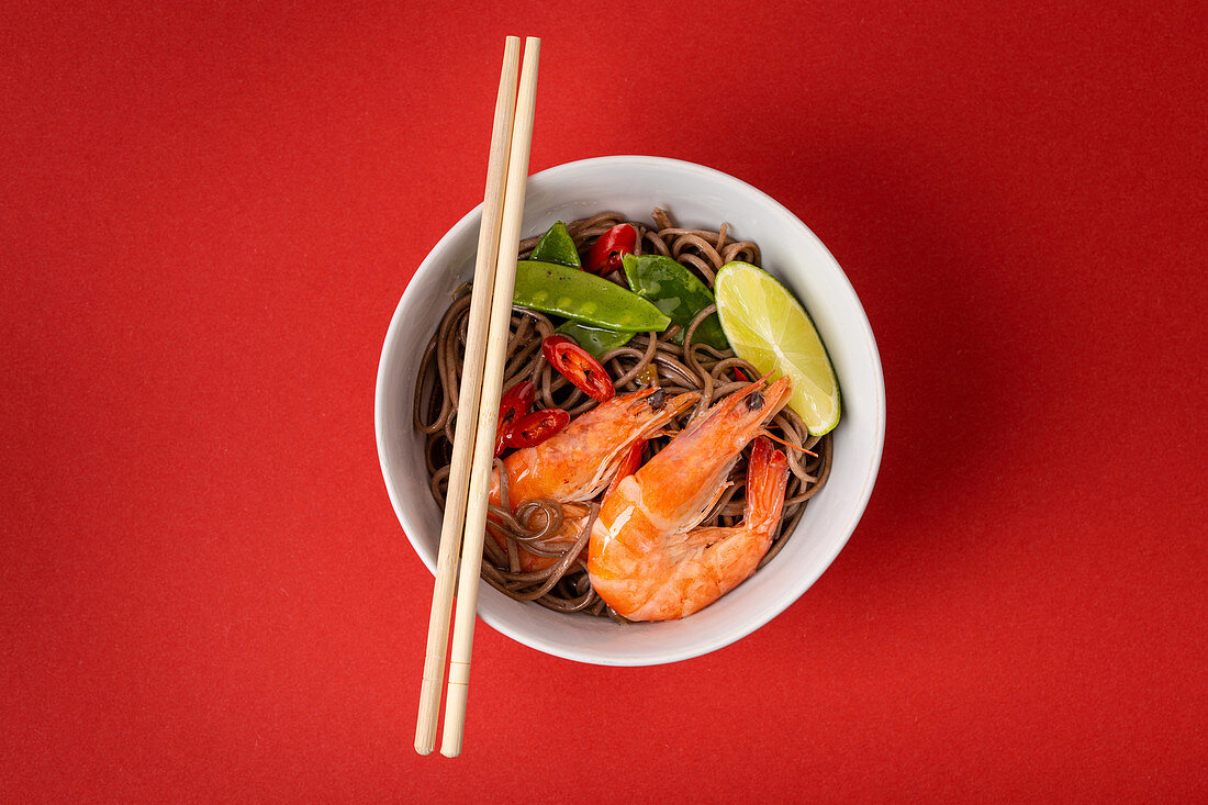 Asian stir fry soba noodles with shrimps, vegetables, green peas, red pepper in white bowl with wooden chopsticks