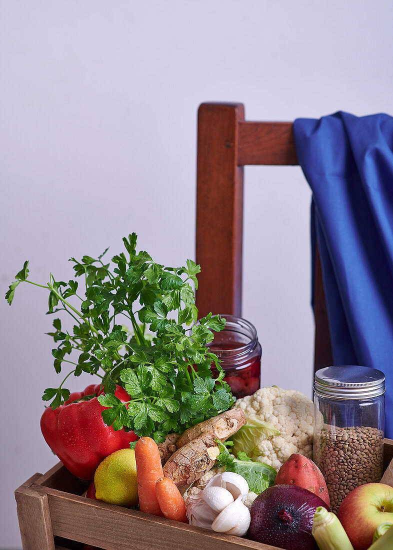 Fresh vegetables, fruit and herbs in a wooden crate on a chair